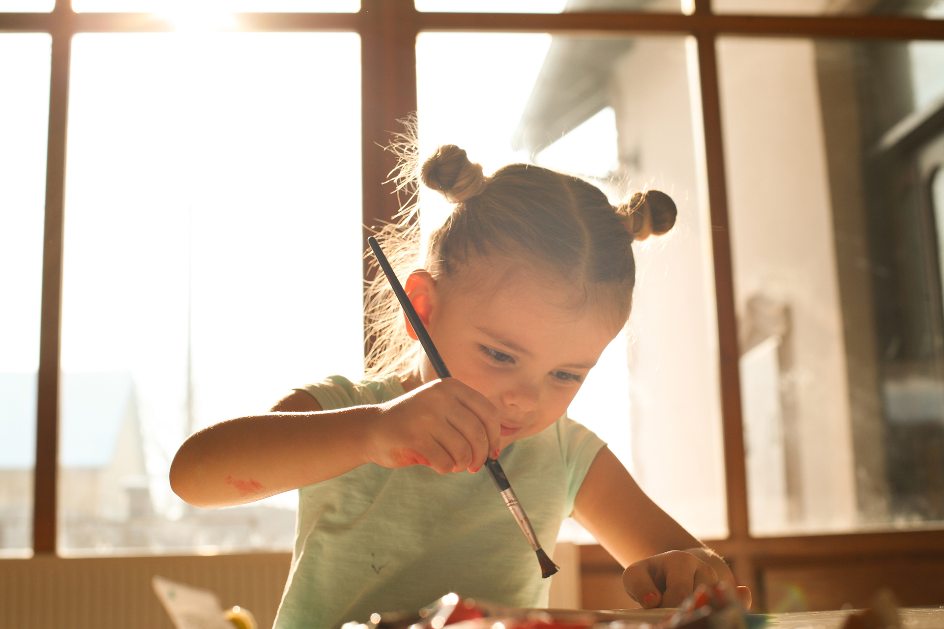 Petite fille en train de peindre et de dessiner : que faire de tous ses dessins d'enfants ?