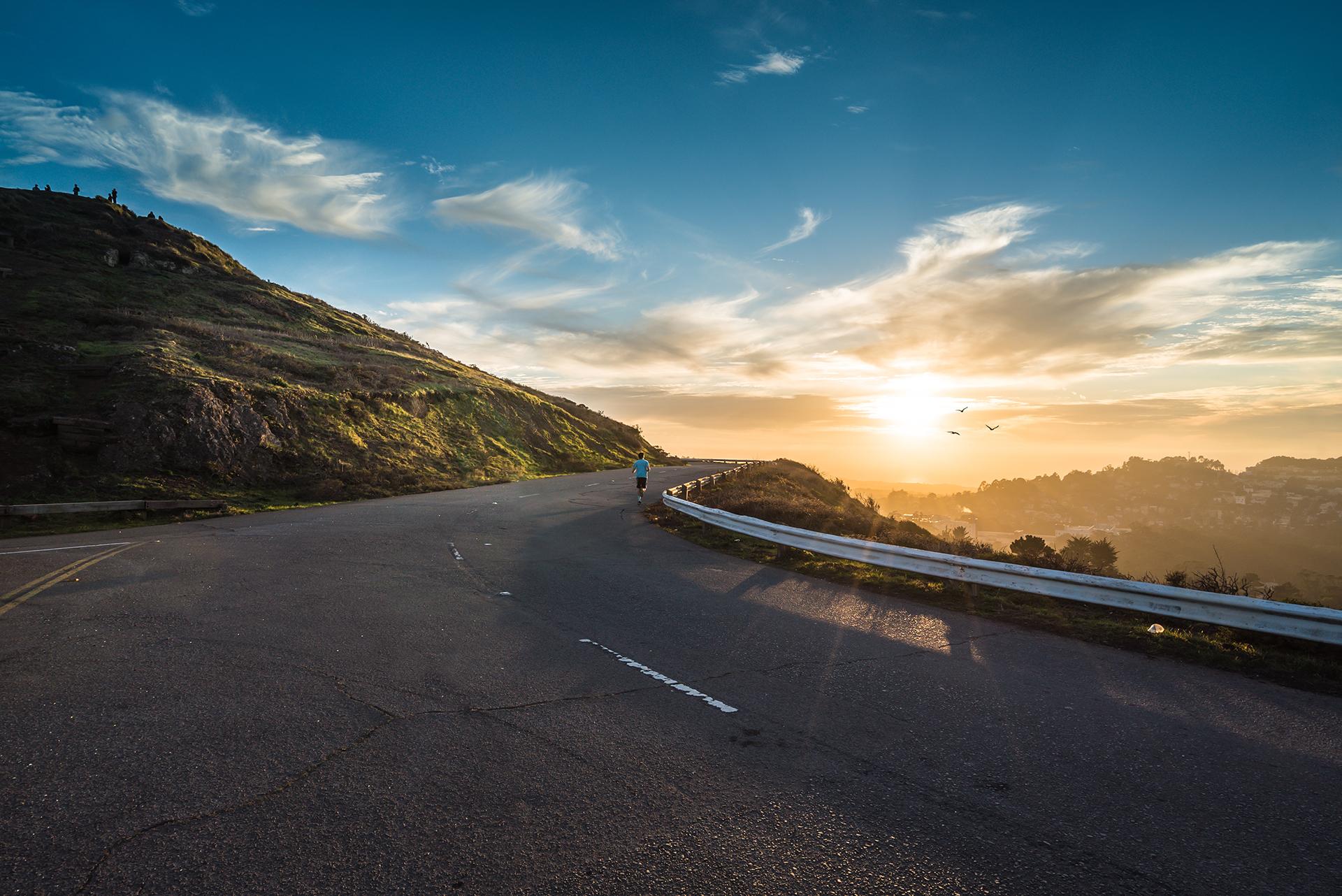 Coucher de soleil sur les montages avec une route et un coureur - Découvrez quatre types de lumières idéales pour prendre une photo