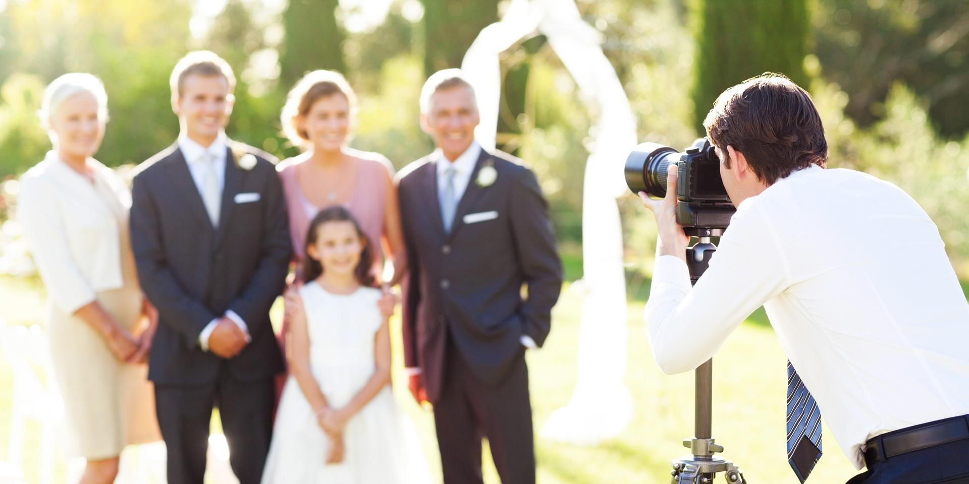 Photographe à un mariage qui prend en photo la famille et les demoiselles d'honneur