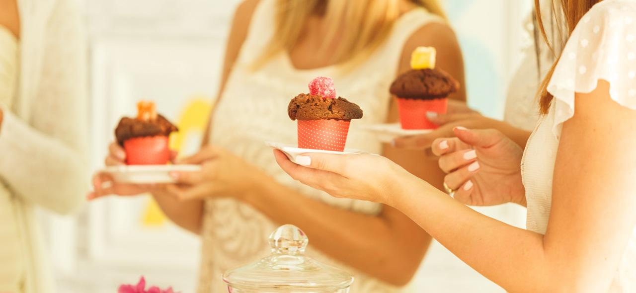 Organisation d'une fête de baby shower avec des femmes tenant des petits gâteaux fait maison