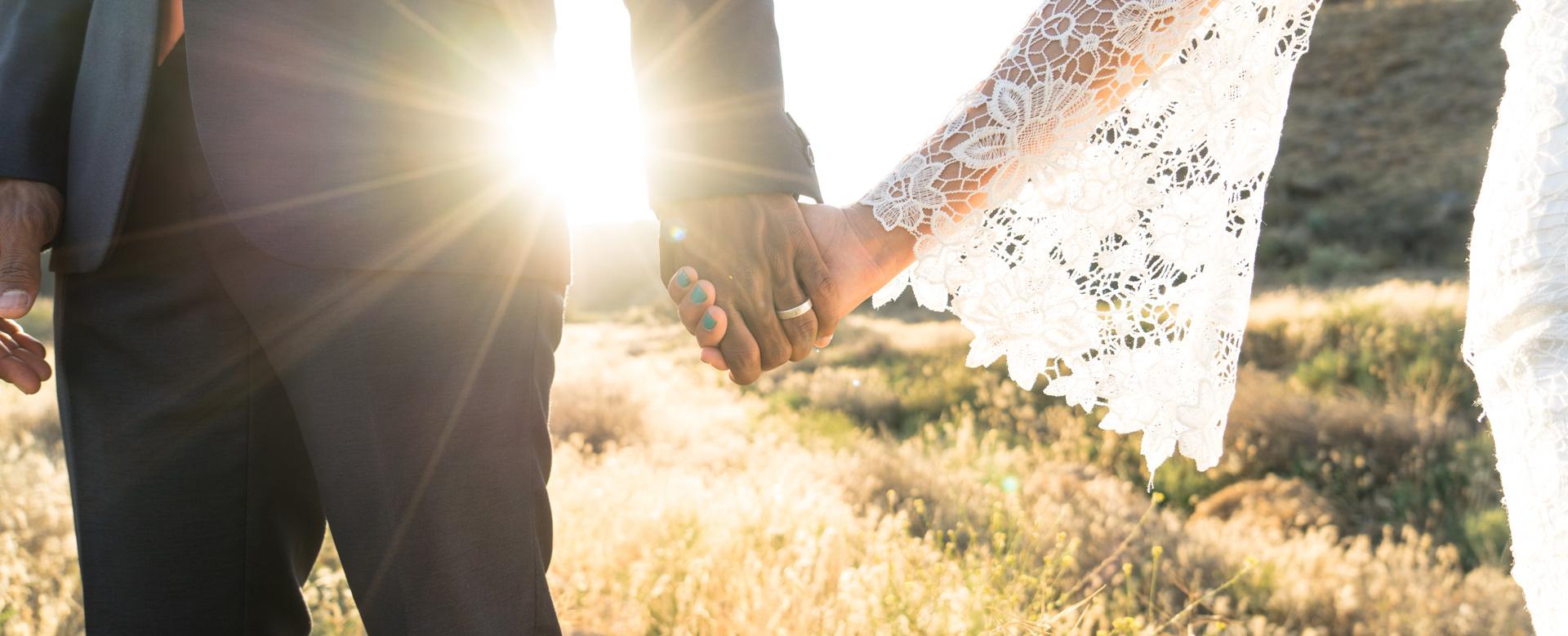 Couple de mariés se tenant la main dans un champ, découvrez le top 5 des meilleurs blogs de mariage dans le monde